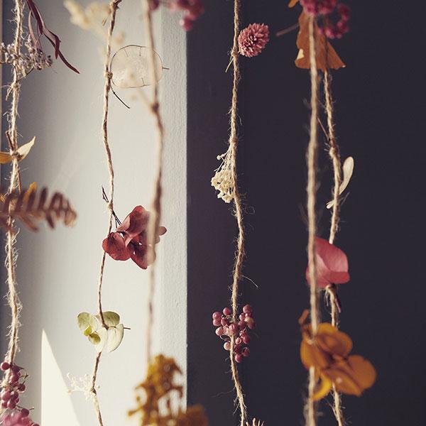 Décoration à base de fleurs séchées et stabilisées sur du fil pendu