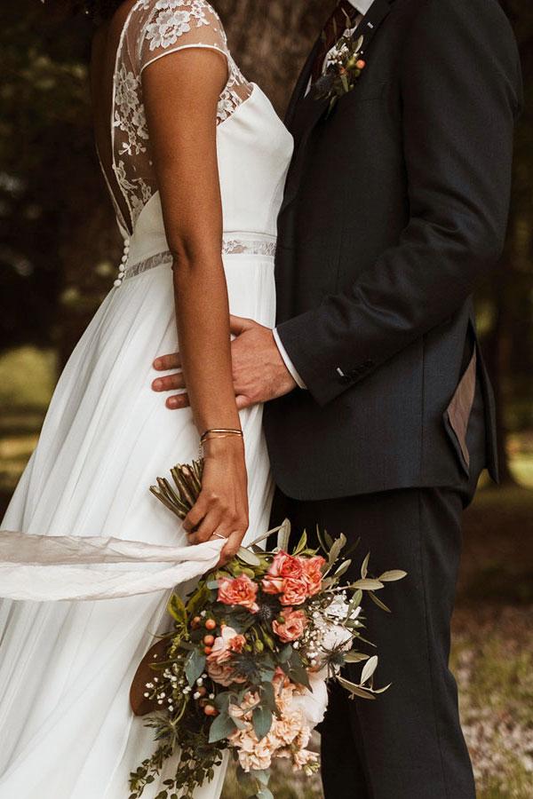 Couple se tenant par la taille portant un bouquet de fleurs