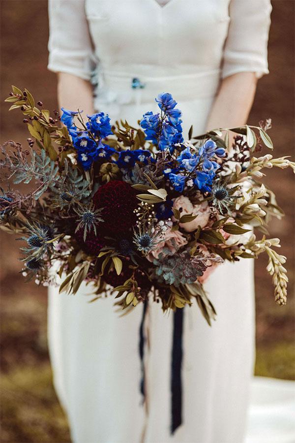 Mariée portant un bouquet de fleurs bleues et blanches