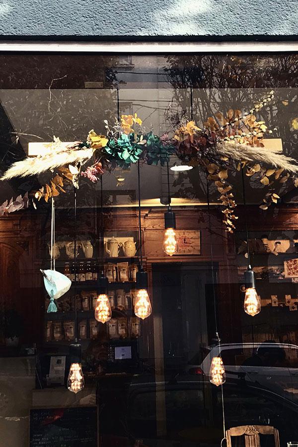 Composition fleurie accrochée à une vitrine de magasin de vin