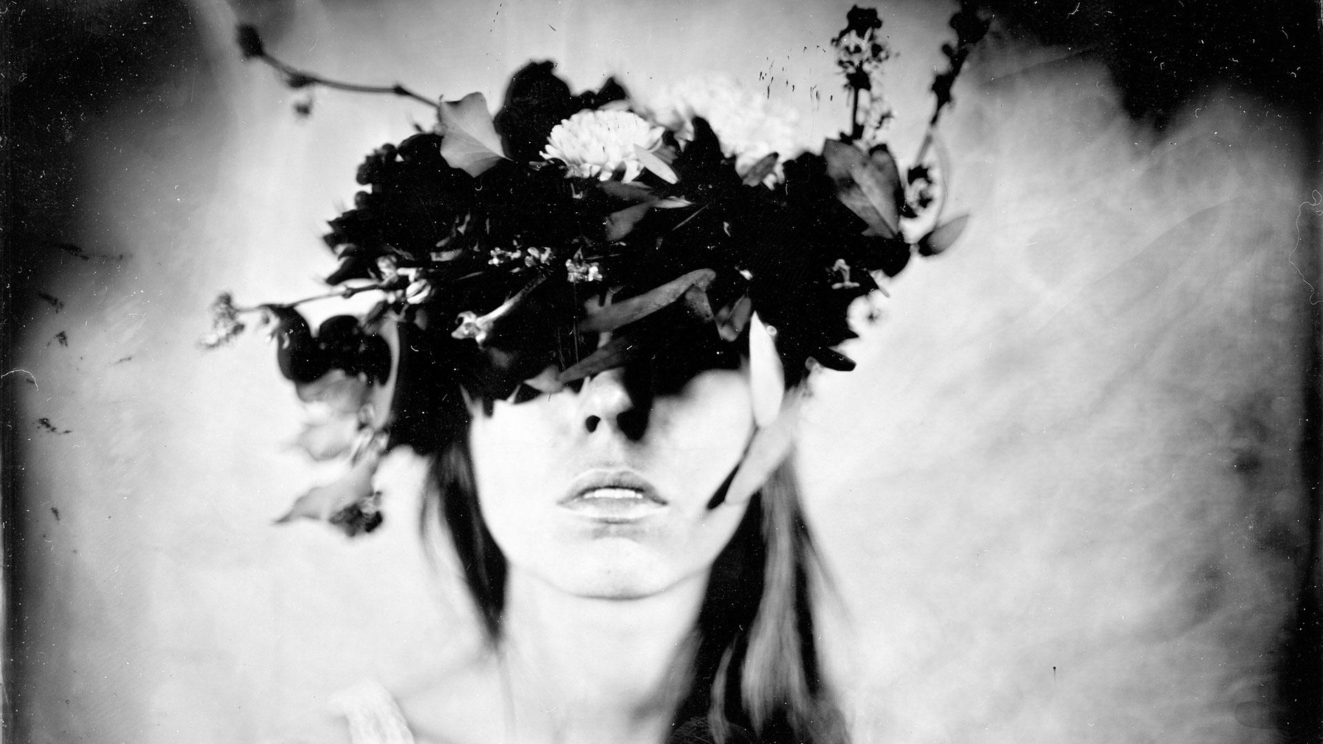 Femme portant une couronne de fleurs sur ses yeux
