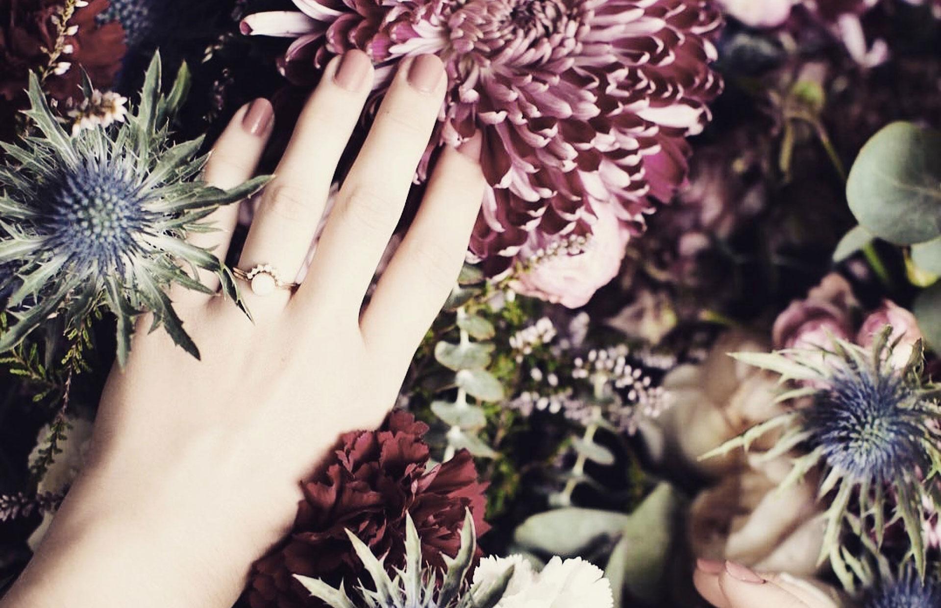 Main de femme avec bague de mariage sur un lit de fleurs